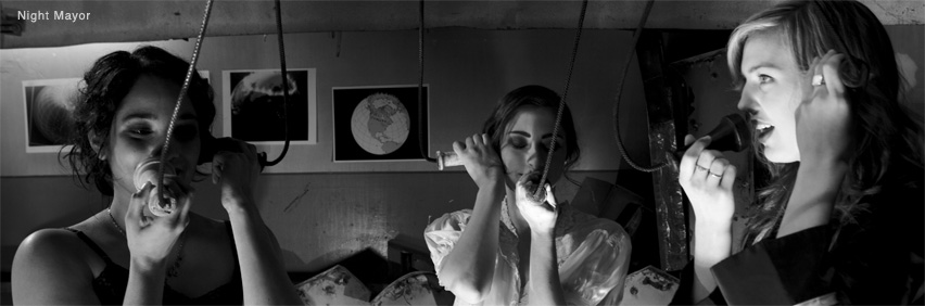 Three young women holding vintage telephones. Photo taken from Night Mayor, an experimental film directed by Guy Maddin in 2009.